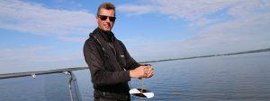Mikael Henriksson tar prover på Vombsjöns vatten