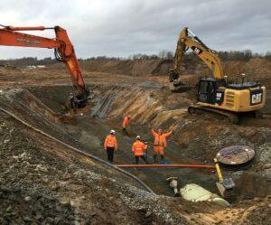 Grävmaskiner jobbar vid en grop för vattenledningen