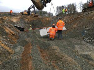 Grävmaskin lyfter betongblock