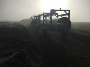 Traktor fraktar råvattenledning i disigt landskap