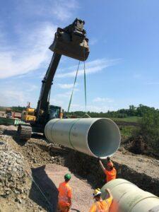 Råvattenledning lyfts på plats av grävmaskin