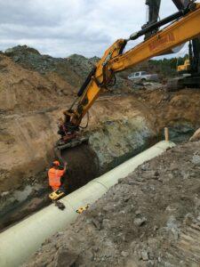 Grävmaskin utför fyllnadsarbete med vråvattenledningen